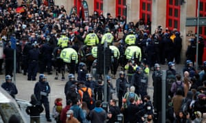 Riot Police officers, including mounted police, form two lines to control the crowd.