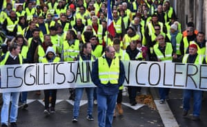 """Protestors show solidarity behind a banner that reads """" Yellow vests are angry""""."""