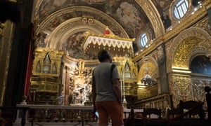 A tourist looks up at the ceiling of St John's Co-Cathedral in Valletta, Malta.