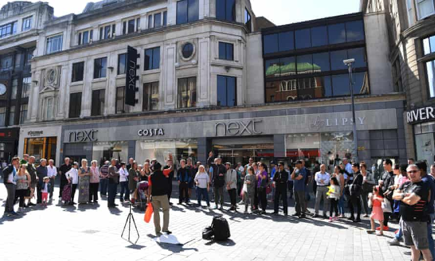 Shoppers watch a street entertainer in Liverpool