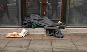 A rough sleeper under a sleeping bag in the Strand, central London.
