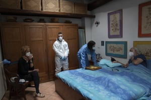 Doctor Elisa Riccitelli talks with 85-year old Giorgio Tagliacarne, in his bed, after he received a dose of Covid vaccine at his home in Rome.