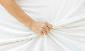 Woman's hand clutching sheet.