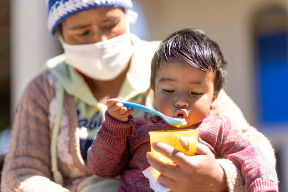A child eats fruit delivered by Unicef and fortified with vitamins with his mother in a village in Guatemala last year.