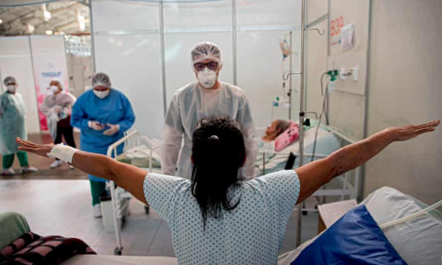 A doctor checks a COVID-19 patient at a field hospital in Belem, Para state, Brazil. For some, a second infection is less severe than the first.
