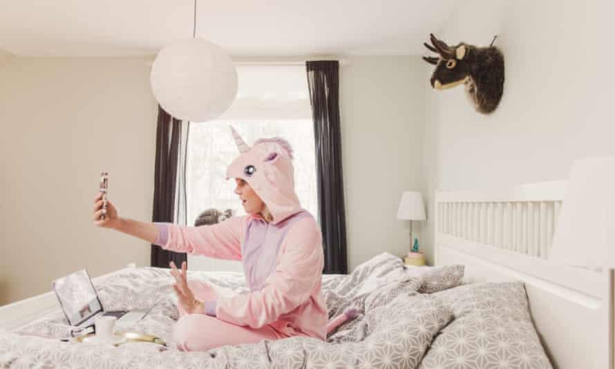 Playful woman in unicorn costume in bedroom