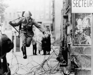 East German soldier Hans Conrad Schumann leaps over a barbed wire barricade at the Bernauer Street sector into West Berlin in August 1961