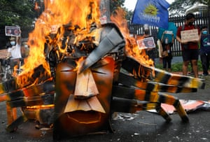 Protesters burn an effigy of the presidential candidate Ferdinand Marcos Jr in Quezon City, Philippines