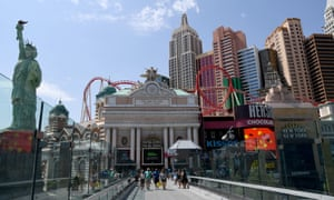 Visitors walk on a pedestrian bridge between MGM Resorts International properties New York-New York Hotel & Casino and MGM Grand Hotel & Casino on the Las Vegas Strip in late August.