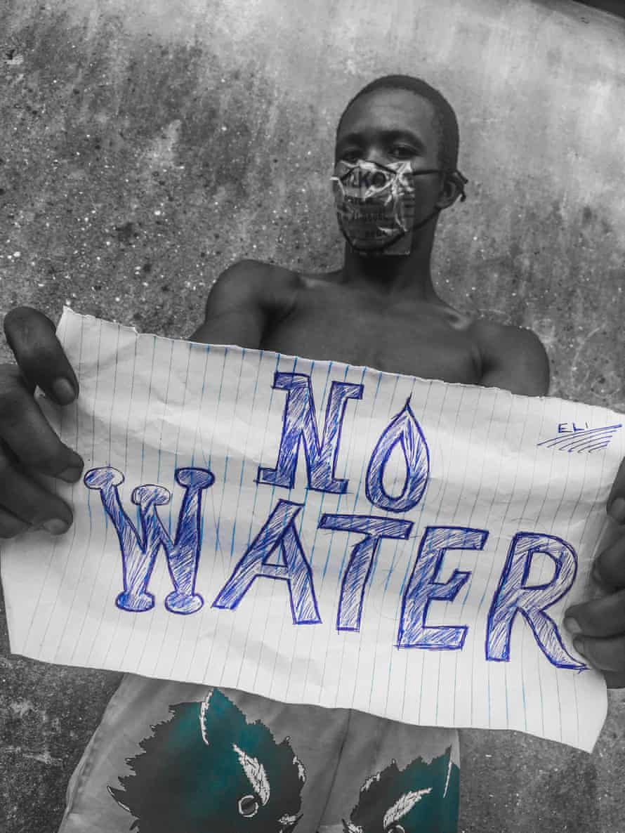 A boy wearing a homemade mask holds a sign, in Orile, Lagos.