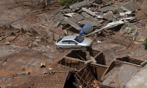 A car sits atop a roof covered in mud and other debris after the collapse of a tailings dam in Brazil.