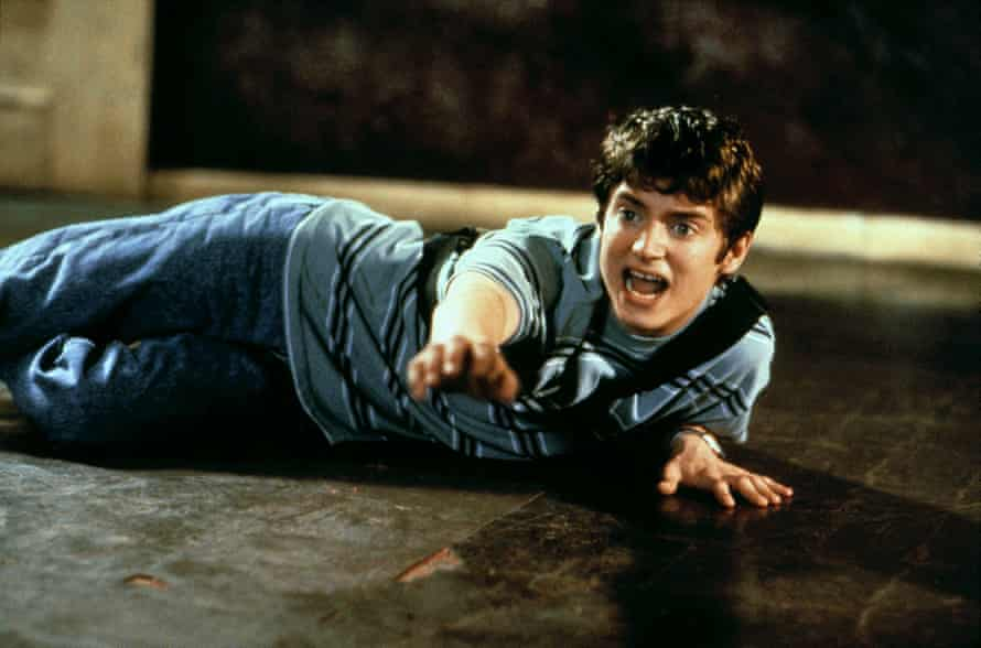 Elijah Wood on the floor yelling and reaching towards an unseen enemy