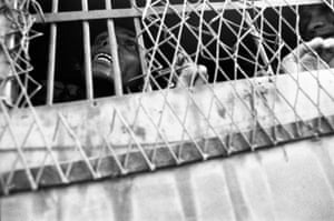 A student who had been picked up in a police raid reaches out from a prison van, Jagannath Hall, Dhaka, Bangladesh, 1996