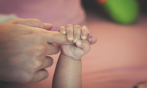 Baby's hand holds mother's finger