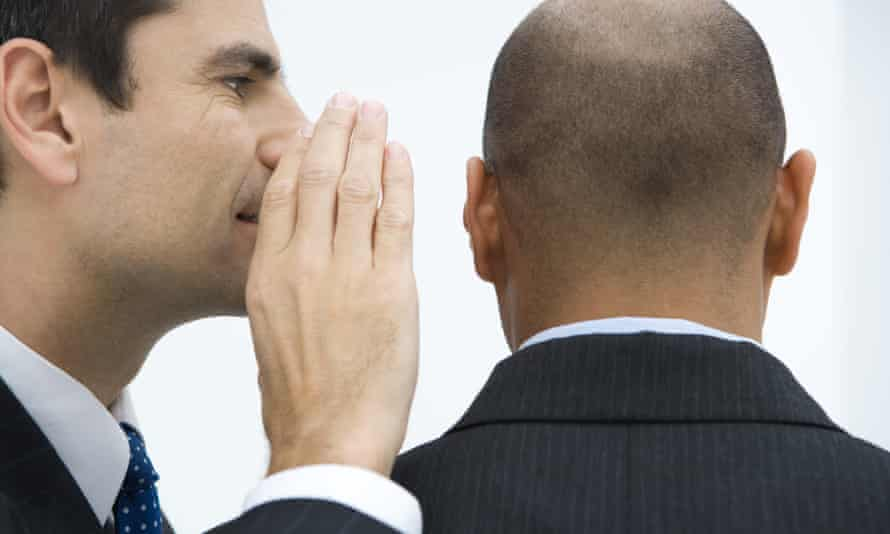 Businessman whispering in colleague's ear