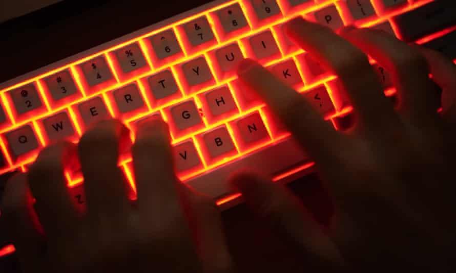 Stock photo of man typing on an illuminated computer keyboard