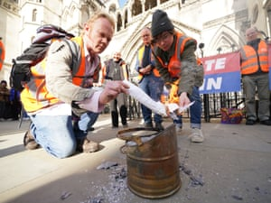 London, UK. Demonstrators from Insulate Britain burn pages from court injunctions outside the high court