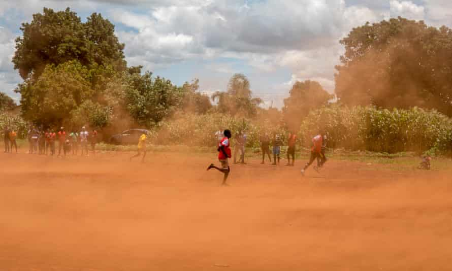 Young boys play a game of soccer on a dusty playing field in Kuwadzana.