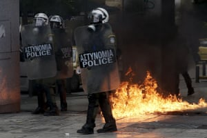 Greek riot police stand by fires caused by petrol bombs thrown by youths following brief clashes between police and protesters during a protest marking a 24-hour strike in Athens, Greece, December 3, 2015. Striking Greek workers will take to the streets on Thursday, disrupting transport, shutting schools and keeping ships docked at port in the second major protest against planned pension cuts in three weeks. REUTERS/Alkis Konstantinidis