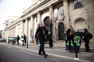 A police officer walks by as activists from the Extinction Rebellion, a global environmental movement, protest outside the Bank of England, in London, Britain, April 1, 2021. REUTERS/Henry Nicholls