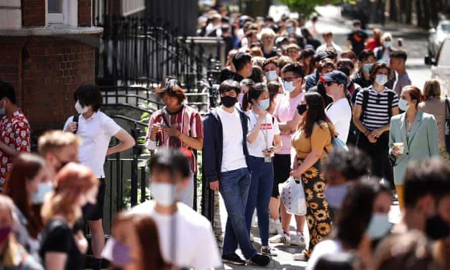 People queue outside a vaccination centre for young people and students in London