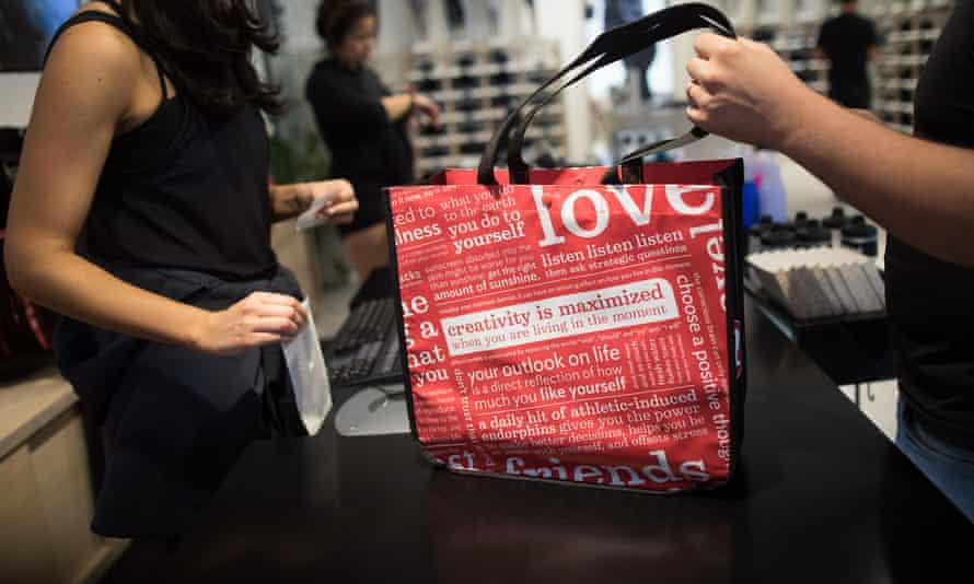 An employee serves a customer at the Lululemon store in London