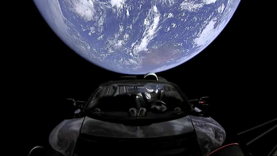 SpaceX shows the company's spacesuit in Elon Musk's red Tesla sports car
