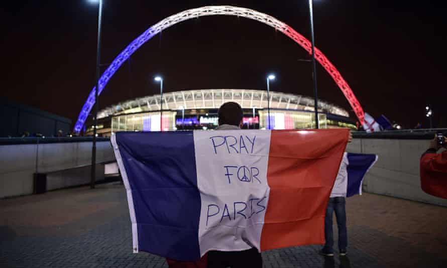A man holds a French flag outside Wembley stadium before the start of the match.