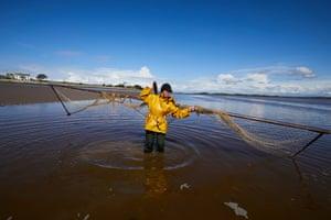 Owen handles her net standing in shallow water
