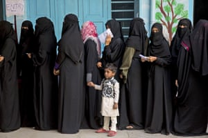 Indian Muslim women stand in a queue to cast their votes during the first state elections in Telangana.