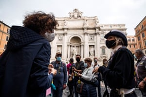 A local police officer checks people and tourists in front of the Fontana di Trevi during the first day since the wearing of protective masks outdoors has become mandatory in the Lazio region amid the coronavirus pandemic in Rome, Italy, on 3 October 2020.