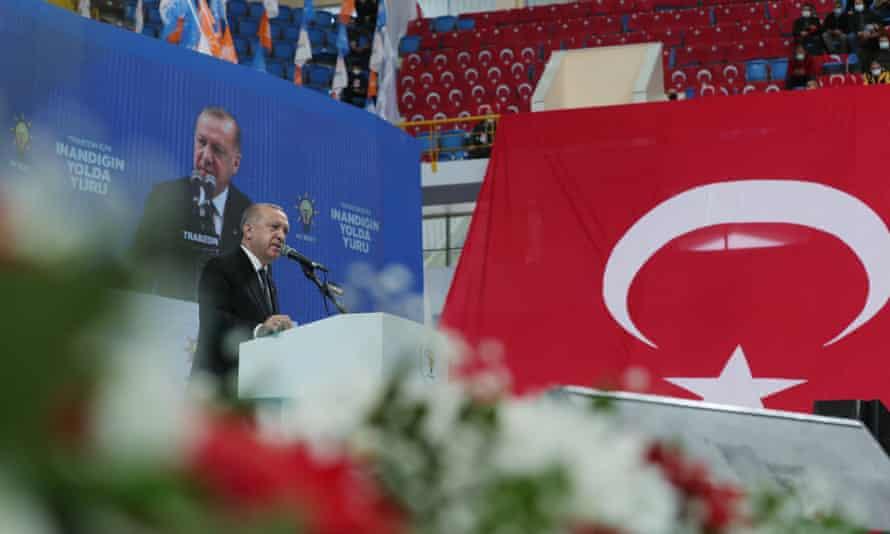 Recep Tayyip Erdoğan on stage with a Turkish flag beside him