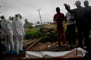 The work of a safe burial team is observed by members of the British military in the Sierra Leonean capital Freetown
