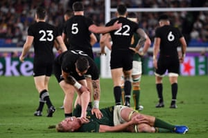 New Zealand's scrum-half TJ Perenara checks on an injured Pieter-Steph Du Toit.
