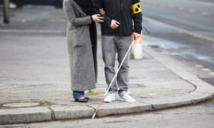 Woman helping a blind man cross a road