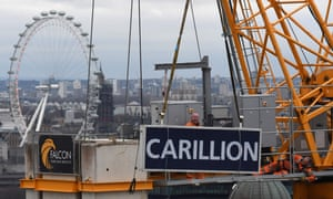 Workers take down a Carillion sign from a crane on a building site in the City of London.
