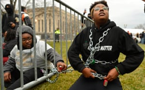 Black Liver Matter protesters chain themselves to an entry point prior at the inauguration