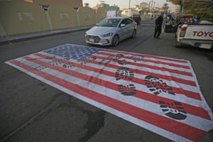 A mock US flag is laid on the ground for cars to drive on in Baghdad