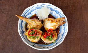 stuffed chicken wings in a bowl with sauce