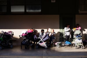 People waiting in line for food at the Second Harvest distribution site at Garfield Elementary School in Menlo Park, California.