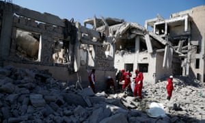 Red Crescent rescue workers search for victims of Saudi coalition airstrikes on a prison complex in Dhamar in Yemen on Sunday.