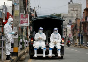 Kathmandu, Nepal. Members of Nepal's army, dressed in PPE, wait to transport the body of a person who died from coronavirus to a crematorium