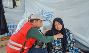 A volunteer doctor listens to a refugee woman's heartbeat