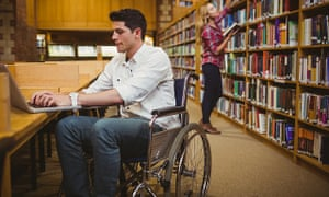 A student in a wheelchair uses his laptop.