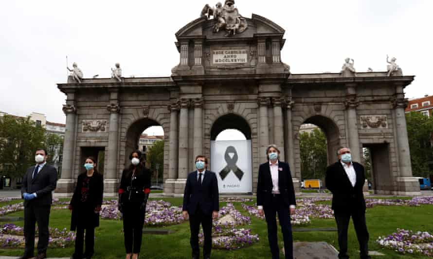 Officials in Madrid observe a minute silence in memory of coronavirus fatalities.