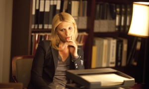 Claire Danes as Carrie Mathison in Homeland sitting and looking contemplative in a study surrounded by books and files