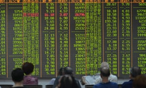 Chinese investors look at share prices of shares at a stock brokerage house in Hangzhou city.
