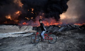A boy passes a burning oil field