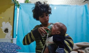 A Syrian boy holds an oxygen mask over the face of an infant at a makeshift hospital following a reported gas attack on the town of Douma in eastern Ghouta.