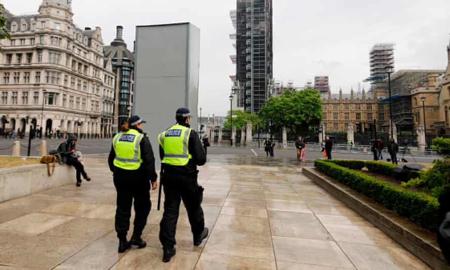 Police officers walk past a boarded-up statue of Winston Churchill on Parliament Square, London.
